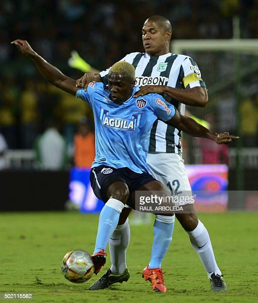 Colombia's Atletico Nacional player Alexis Henriquez vies for the ball with Junior player Edinson Tolza during their Colombian Football League final...
