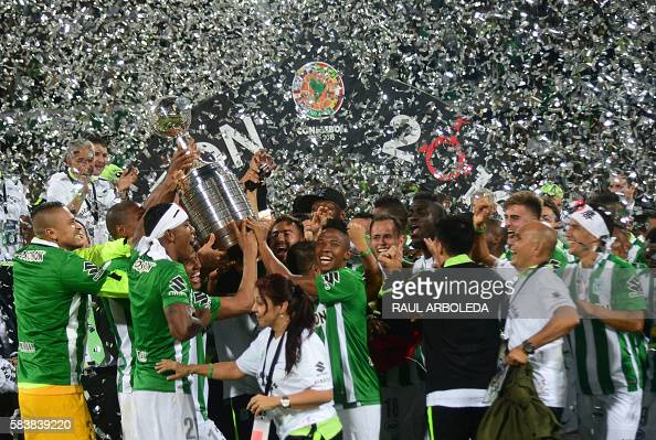 TOPSHOT Colombia's Atletico Nacional players celebrate with the trophy after winning the 2016 Copa Libertadores at Atanasio Girardot stadium in...