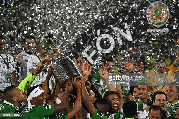 TOPSHOT Colombia's Atletico Nacional players hold the trophy after winning the 2016 Copa Libertadores at Atanasio Girardot stadium in Medellin...