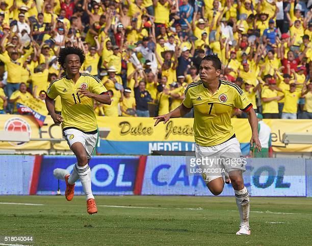 Colombia's Carlos Bacca celebrates next to Juan Cuadrado after scoring against Ecuador during their Russia 2018 FIFA World Cup South American...