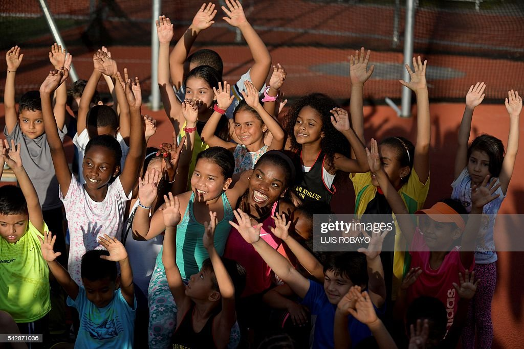 Colombia's Caterine Ibarguen (C) poses for a photo with her fans during a training session prior to the International Athletics Grand Prix at Athletics Stadium Pedro Grajales in Cali, Colombia, on June 24, 2016. / AFP / LUIS