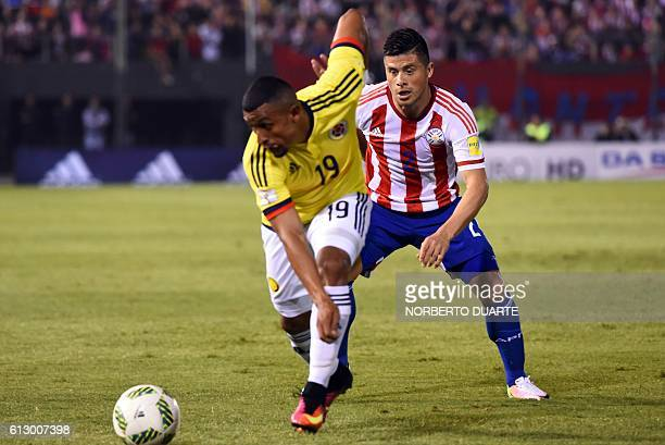 Colombia's defender Farid Diaz is marked by Paraguay's defender Jorge Moreira during their Russia 2018 World Cup football qualifier match in Asuncion...