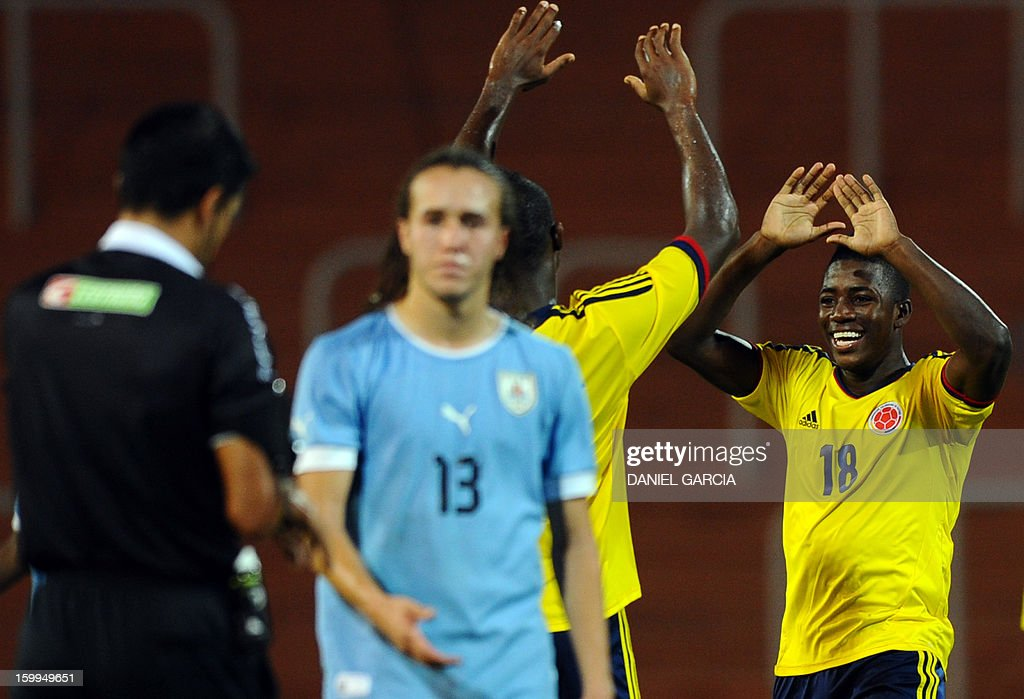 Colombia's defender Julian Figueroa and defender Delvy Balanta celebrate at the end of their South American U-20 final round football match against Uruguay at Malvinas Argentinas stadium in Mendoza, Argentina, on January 23, 2013. Four teams will qualify for the FIFA U-20 World Cup Turkey 2013. AFP PHOTO / DANIEL GARCIA