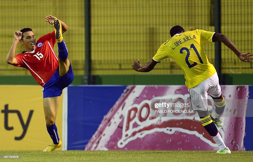 Colombia's defender Luis Orejuela (L) kicks the ball marked by Chile's midfielder Cristian Cuevas during the South American U-20 football match at Domingo Burgueno stadium in Maldonado, 130 km east of Montevideo, on January 19, 2015.