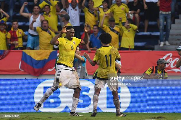 Colombia's defender Yerry Mina celebrates with midfielder Juan Cuadrado after scoring against Uruguay during their Russia 2018 World Cup qualifier...