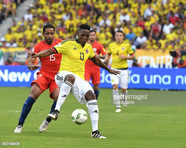 Colombia's defender Yerry Mina is marked by Chile's Jean Beausejour during their 2018 FIFA World Cup qualifier football match in Barranquilla...