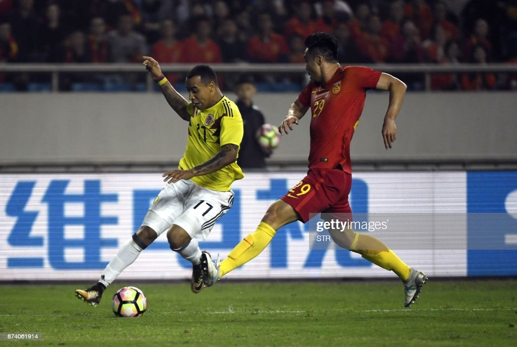 Colombia's Felipe Pardo (L) vies for the ball with China's Zhao Xuri during their international friendly football match in Chongqing, southwest China on November 14, 2017. A Colombia side missing James Rodriguez punished China 4-0 away in a friendly on November 14 as coach Jose Pekerman made wholesale changes from the team defeated in acrimony in South Korea. / AFP PHOTO / STR / China OUT