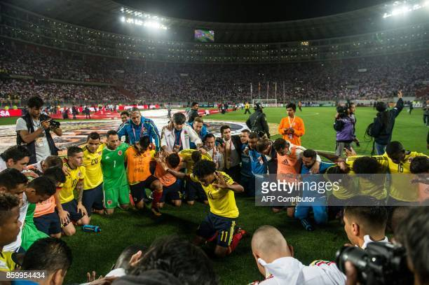 Colombia's footballer Juan Cuadrado leads a prayer after his team qualified for the 2018 World Cup in a tied match with Peru in Lima on October 10...