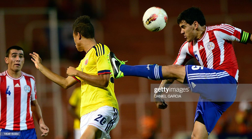 Colombia's forward Brayan Perea vies for the ball with Paraguay's defender Gustavo Gomez (R), during their South American U-20 final round football match at Malvinas Argentinas stadium in Mendoza, Argentina, on February 3, 2013. Paraguay, Colombia, Uruguay and Chile qualified for the FIFA U-20 World Cup Turkey 2013.