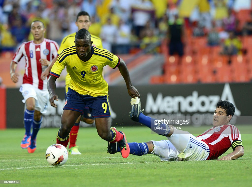 Colombia's forward Jhon Cordoba (L) dribbles Paraguay's defender Gustavo Gomez to shoot and score the first goal, during their South American U-20 Championship Group A football match, at Malvinas Argentinas stadium in Mendoza, Argentina, on January 9, 2013 . Four teams will qualify for the FIFA U-20 World Cup Turkey 2013. AFP PHOTO / DANIEL GARCIA