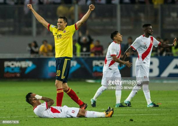 Colombia's Giovanni Moreno celebrates as well as Peru's Christian Ramos Raul Ruidiaz and Christian Cueva after the match ended with a draw 11 during...