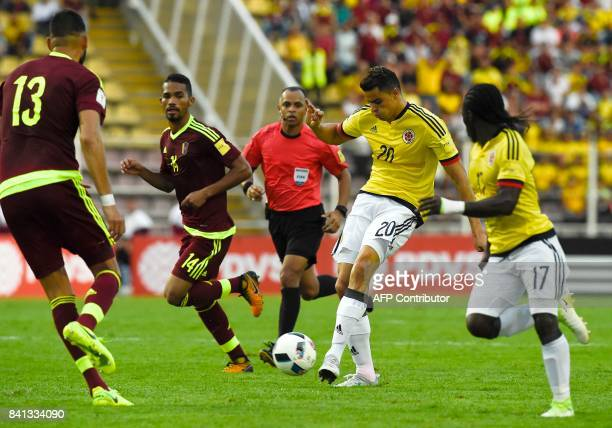 Colombia's Giovanni Moreno prepares to shoot against Venezuela's Jhon Chancellor and Venezuela's Yangel Herrera during their 2018 World Cup qualifier...