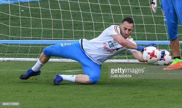 Colombia's goalie David Ospina stops a shot during a training session at the Metropolitano Stadium in Barranquilla on March 21 2017 ahead of their...