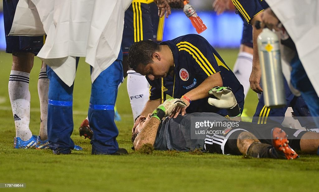 Colombia's goalkeeper David Ospina is assisted during the Brazil 2014 FIFA World Cup South American qualifier match against Ecuador, in Barranquilla, Colombia, on September 6, 2013. AFP PHOTO / LUIS ACOSTA