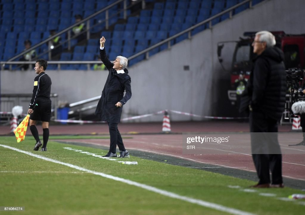 Colombia's head coach Jose Pekerman (C) gestures as China's head coach Marcello Lippi (R) looks on during their international friendly football match in Chongqing, southwest China on November 14, 2017. A Colombia side missing James Rodriguez punished China 4-0 away in a friendly on November 14 as coach Jose Pekerman made wholesale changes from the team defeated in acrimony in South Korea. / AFP PHOTO / STR / China OUT
