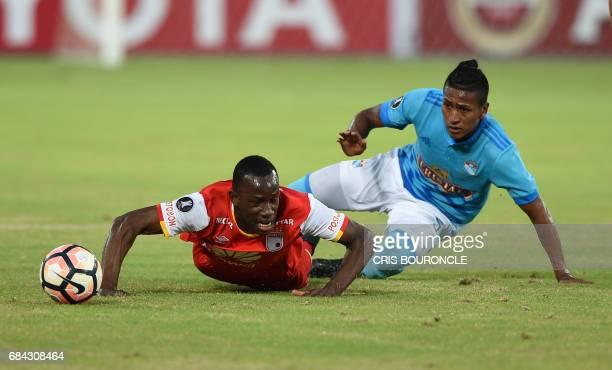 Colombias Independiente Santa Fe player Baldomero Perlaza vies for the ball with Peru's Sporting Cristal Pedro Aquino during their Copa Libertadores...