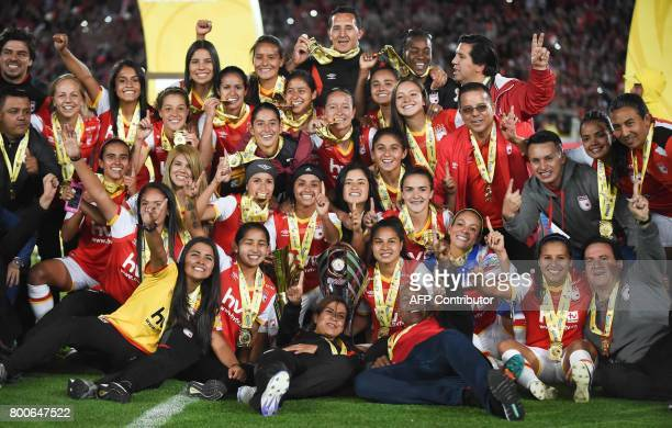 Colombia's Independiente Santa Fe players pose for photos while celebrating after winning their Women's Football League championship final match...