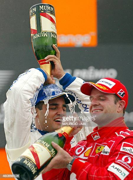 Colombia's Juan Pablo Montoya sprays champagne on his own head while Brazilian Rubens Barrichello drinks celebrating the victory and the third place...