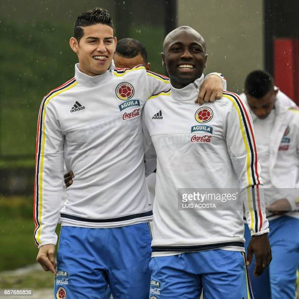 Colombia's midfielder James Rodriguez and defender Pablo Armero joke before a training session at the Colombian football Federation in Bogota on...