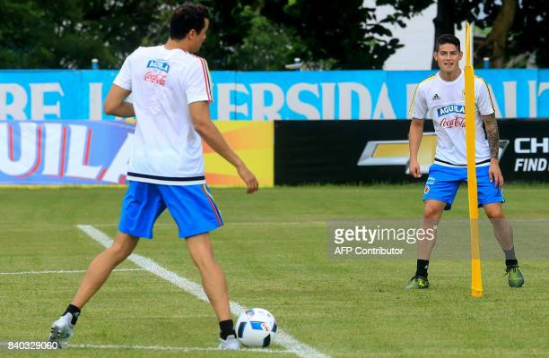 Colombia's midfielder James Rodriguez and Giovanny Moreno take part in a training session in Barranquilla on August 28 2017 ahead of their FIFA World...