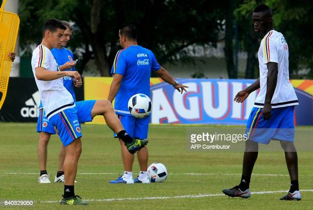 Colombia's midfielder James Rodriguez controls the ball next to Davison Sanchez during a training session in Barranquilla on August 28 2017 ahead of...