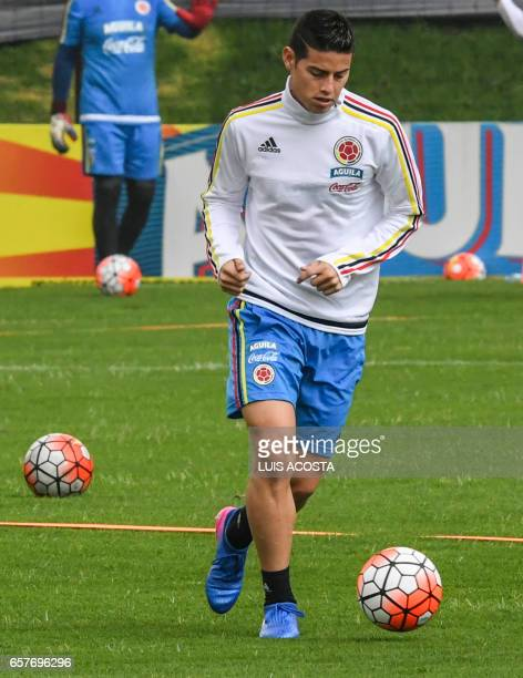 Colombia's midfielder James Rodriguez runs with the football during a training session at the Colombian football Federation in Bogota on March 25...