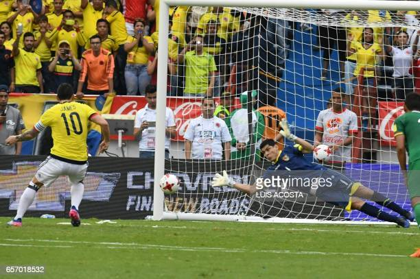Colombia's midfielder James Rodriguez scores a penalty kick against Bolivia's goalkeeper Carlos Lampe during their 2018 FIFA World Cup qualifier...