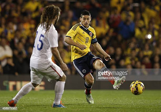 Colombia's midfielder James Rogriguez passes the ball past US midfielder Kyle Becherman during the friendly international football match between...