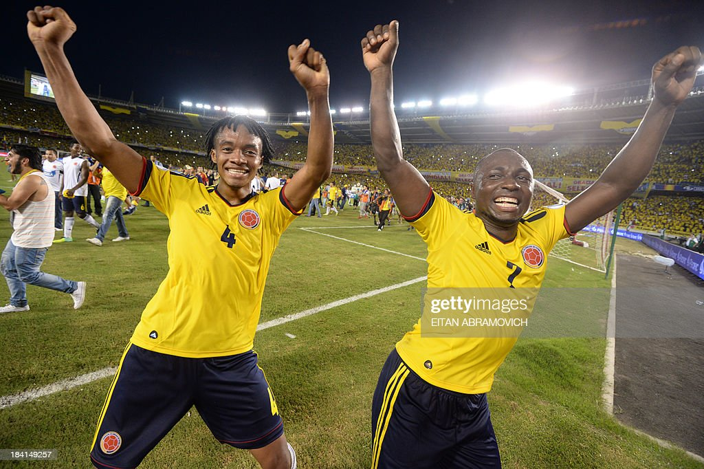 Colombia's midfielder Juan Cuadrado (L) and defender Pablo Armero celebrate after qualifying for the Brazil 2014 FIFA World Cup after a 3-3 tie with Chile in a South American qualifier match, in Barranquilla, Colombia, on October 11, 2013. AFP PHOTO / EITAN ABRAMOVICH