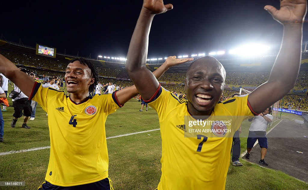 Colombia's midfielder Juan Cuadrado (L) and defender Pablo Armero celebrate after qualifying for the Brazil 2014 FIFA World Cup after a 3-3 tie with Chile in a South American qualifier match, in Barranquilla, Colombia, on October 11, 2013.