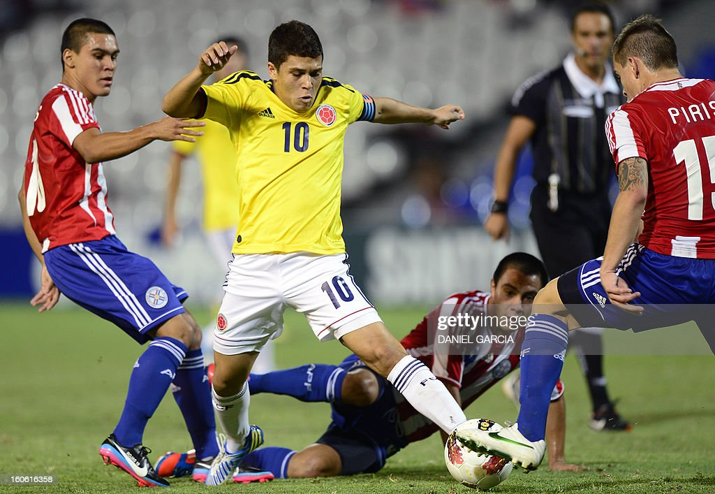 Colombia's midfielder Juan Quintero (C) vies for the ball with Paraguay's midfielder Jorge Rojas (L), midfielder Angel Cardozo and midfielder Robert Piris, during their South American U-20 final round football match at Malvinas Argentinas stadium in Mendoza, Argentina, on February 3, 2013. Paraguay, Colombia, Uruguay and Chile qualified for the FIFA U-20 World Cup Turkey 2013.