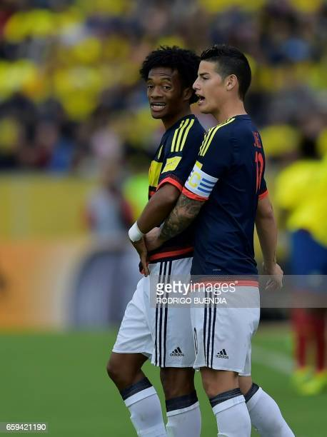 Colombia's midfielders James Rodriguez and Juan Cuadrado chat during their 2018 FIFA World Cup qualifier football match against Ecuador in Quito on...