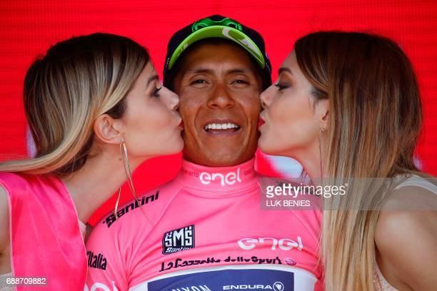 Colombia's Nairo Quintana of Movistar team is kissed by hostesses as he celebrates his overall leader pink jersey on the podium at the end of the...