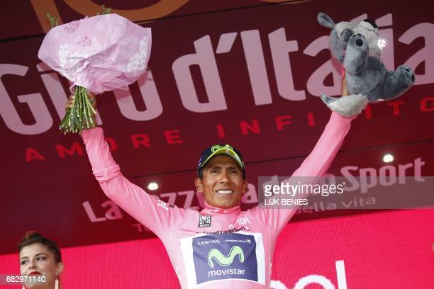 Colombia's Nairo Quintana of team Movistar celebrates the pink jersey of the overall leader on the podium after winning the 9th stage of the 100th...