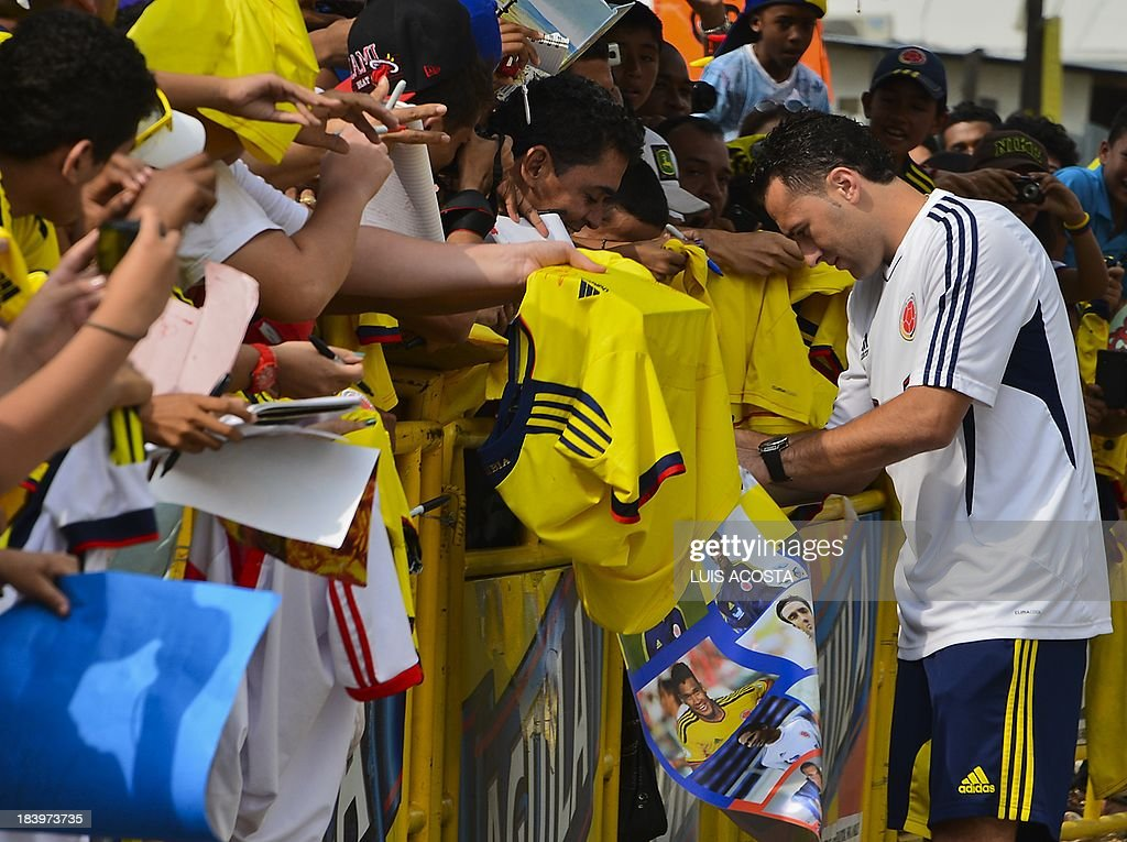 Colombia's national football team player David Ospina autographs t-shirts to fans before a training session in Barranquilla, Colombia, on October 10, 2013. Colombia will face Chile in a FIFA World Cup Brazil 2014 qualifier match on October 11. AFP PHOTO/Luis Acosta