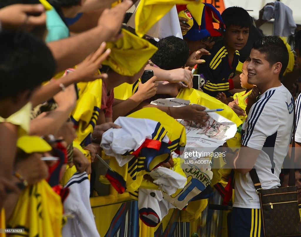 Colombia's national football team player James Rodriguez signs T-shirts to fans before a training session in Barranquilla, Colombia, on October 9, 2013. Colombia will face Chile in a FIFA World Cup Brazil 2014 qualifier match on September 11. AFP PHOTO/Luis Acosta