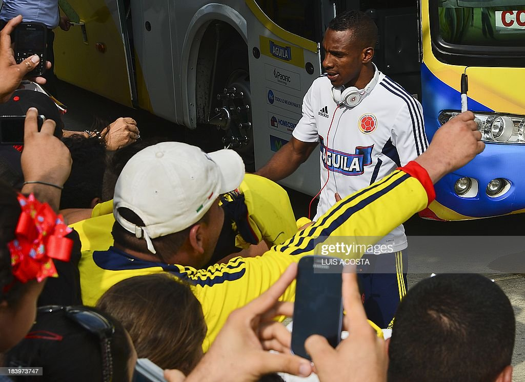 Colombia's national football team player Luis Amaranto Perea autographs t-shirts to fans before a training session in Barranquilla, Colombia, on October 10, 2013. Colombia will face Chile in a FIFA World Cup Brazil 2014 qualifier match on October 11. AFP PHOTO/Luis Acosta
