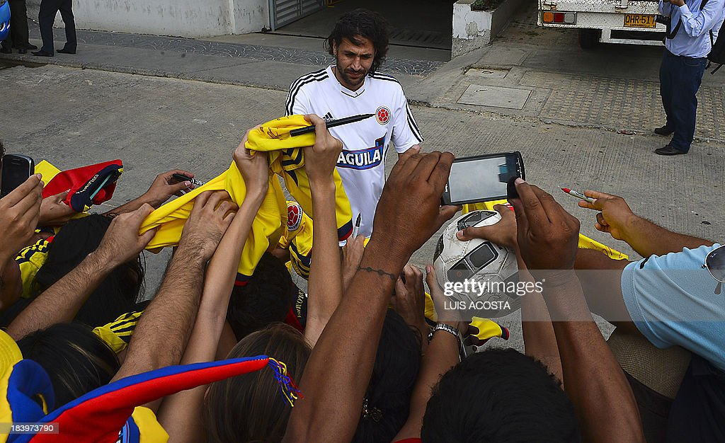 Colombia's national football team player Mario Yepes autographs t-shirts to fans before a training session in Barranquilla, Colombia, on October 10, 2013. Colombia will face Chile in a FIFA World Cup Brazil 2014 qualifier match on October 11. AFP PHOTO/Luis Acosta