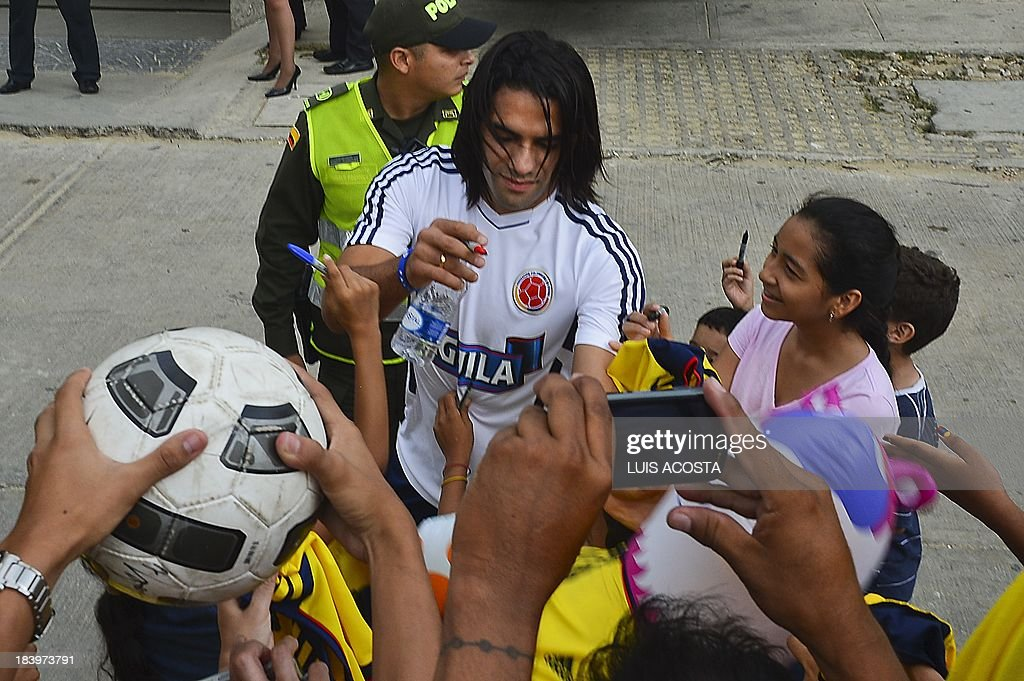 Colombia's national football team player Radamel Falcao Garcia autographs t-shirts to fans before a training session in Barranquilla, Colombia, on October 10, 2013. Colombia will face Chile in a FIFA World Cup Brazil 2014 qualifier match on October 11. AFP PHOTO/Luis Acosta