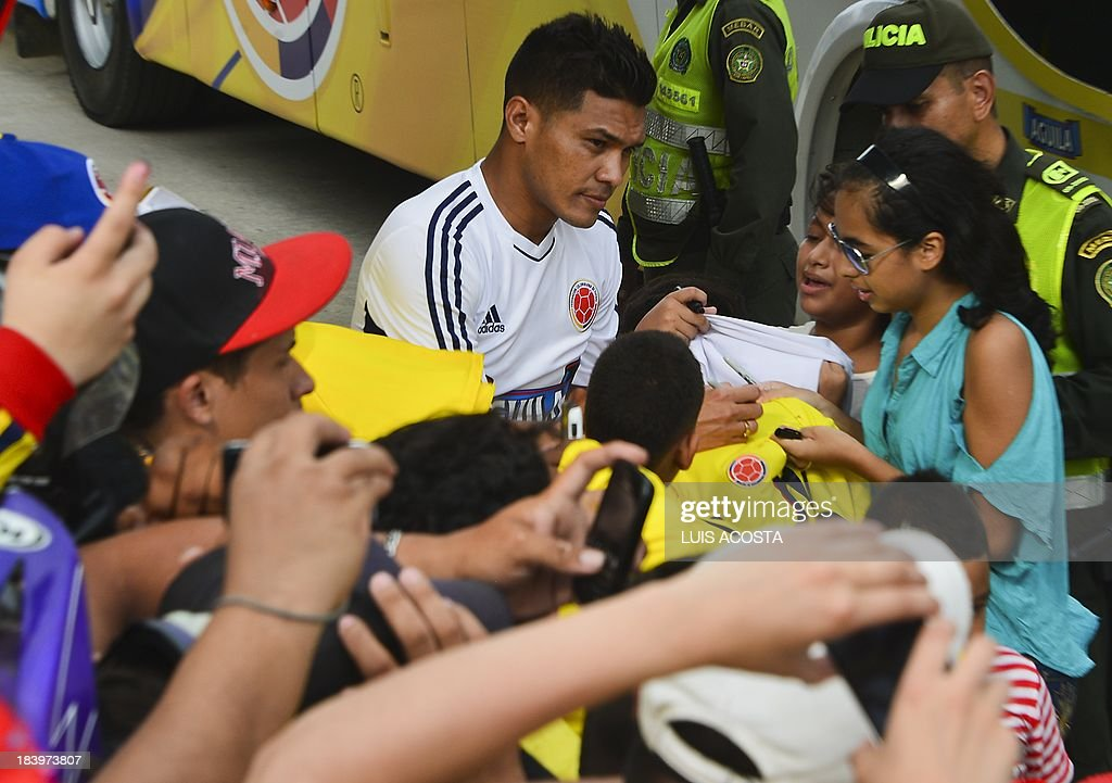 Colombia's national football team player Teofilo Gutierrez autographs t-shirts to fans before a training session in Barranquilla, Colombia, on October 10, 2013. Colombia will face Chile in a FIFA World Cup Brazil 2014 qualifier match on October 11. AFP PHOTO/Luis Acosta
