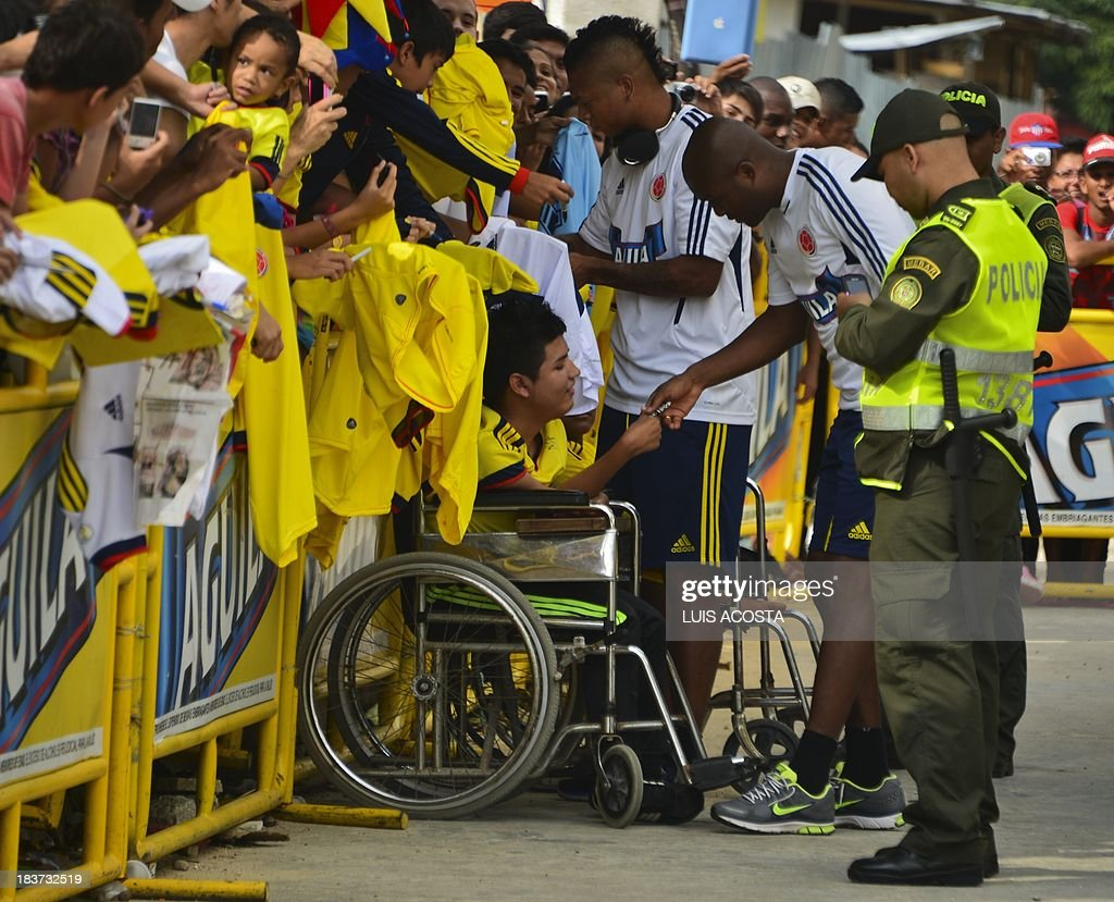 Colombia's national football team players Aquivaldo Mosquera (L) and Fredy Guarin sign T-shirts to fans before a training session in Barranquilla, Colombia, on October 9, 2013. Colombia will face Chile in a FIFA World Cup Brazil 2014 qualifier match on September 11. AFP PHOTO/Luis Acosta