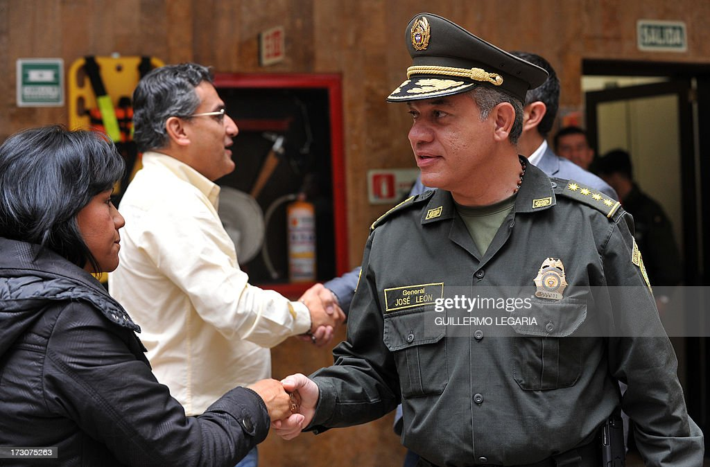Colombia's National Police Chief Gen. Jose Roberto Leon Riano (R) shakes hands with journalists before a press conference at the National Police headquarters in Bogota, on July 6, 2013 to give details about the capture of Roberto Pannunzi (65), an Italian mafia capo allegedly the world biggest cocaine trafficker who was arrested on the eve. Pannunzi who fled from a Rome prison in 2010, was detained in a shopping mall in Bogota with a fake Venezuelan identity card in a joint operation by Colombian police and the US Drug Enforcement Administration (DEA) and was deported on Friday night to Italy. AFP PHOTO/Guillermo LEGARIA