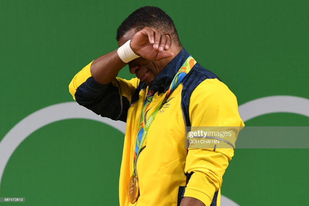 TOPSHOT - Colombia's Oscar Albeiro Figueroa Mosquera cries on the podium after he won the Men's 62kg weightlifting competition at the Rio 2016 Olympic Games in Rio de Janeiro on August 8, 2016. / AFP / GOH Chai Hin