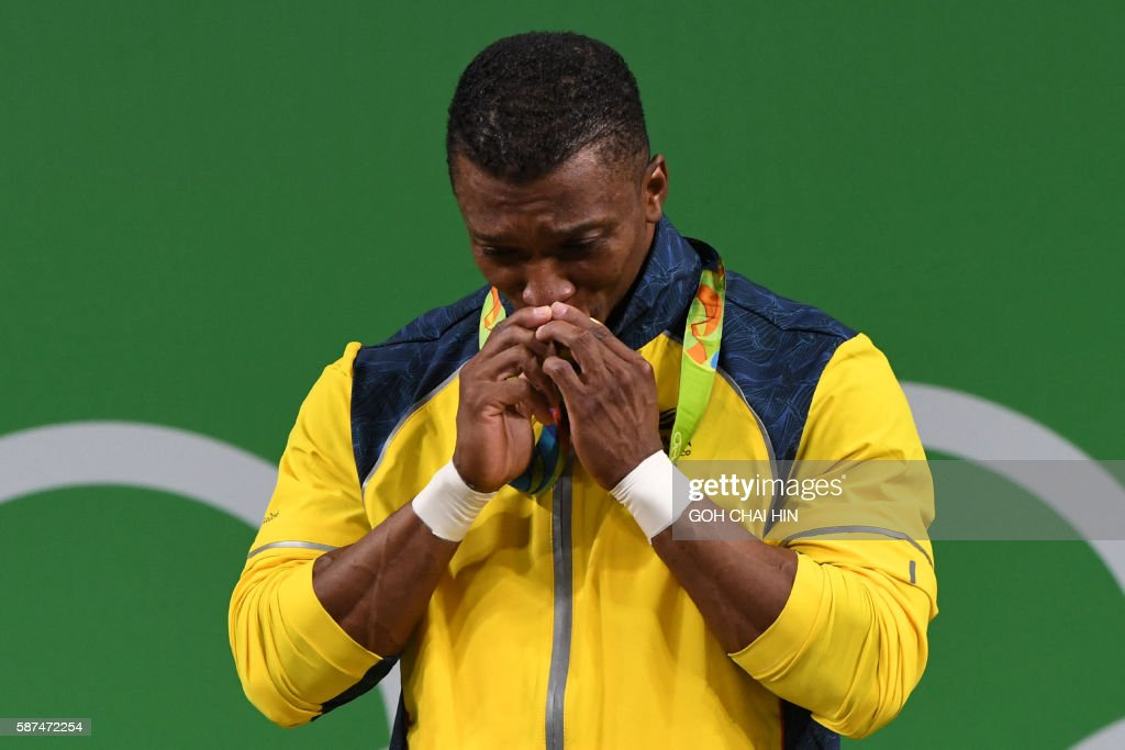 Colombia's Oscar Albeiro Figueroa Mosquera kisses his gold medal while standing on the podium of the Men's 62kg weightlifting competition at the Rio 2016 Olympic Games in Rio de Janeiro on August 8, 2016. / AFP / GOH Chai Hin