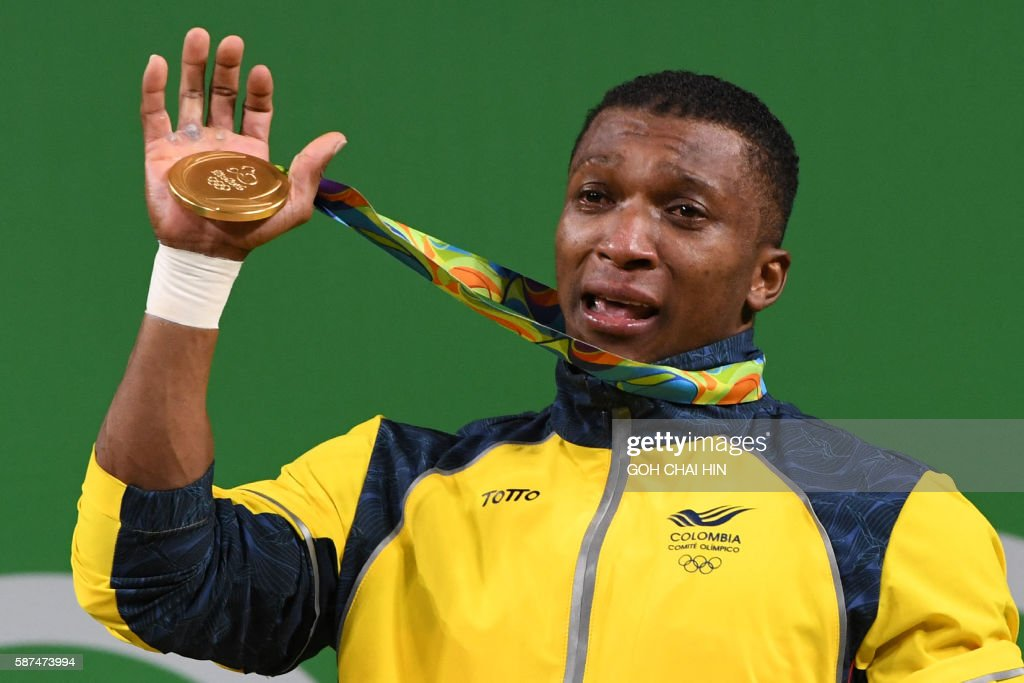 Colombia's Oscar Albeiro Figueroa Mosquera poses with his gold medal on the podium of the Men's 62kg weightlifting competition at the Rio 2016 Olympic Games in Rio de Janeiro on August 8, 2016. / AFP / GOH Chai Hin