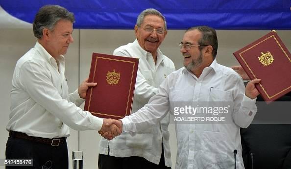TOPSHOT Colombia's President Juan Manuel Santos and Timoleon Jimenez aka 'Timochenko' head of the FARC leftist guerrilla shake hands accompanied by...