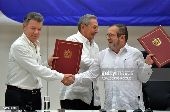 Colombia's President Juan Manuel Santos and Timoleon Jimenez aka 'Timochenko' head of the FARC leftist guerrilla shake hands accompanied by Cuban...