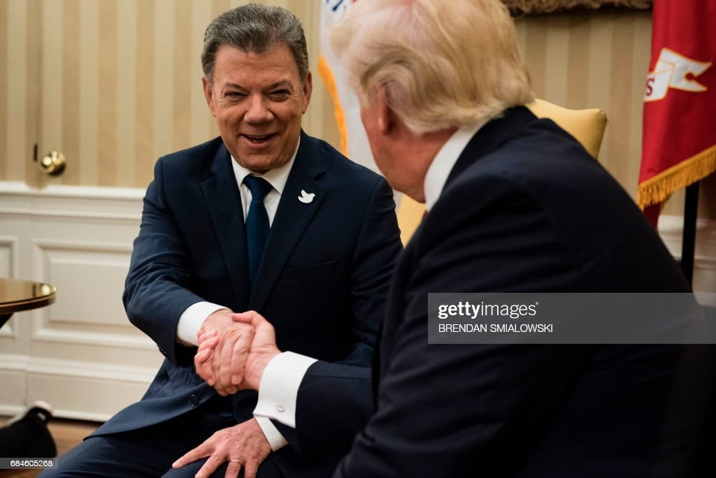 Colombia's President Juan Manuel Santos and US President Donald Trump shake hands before a meeting in the Oval Office of the White House May 18, 2017 in Washington,DC. / AFP PHOTO / Brendan Smialowski