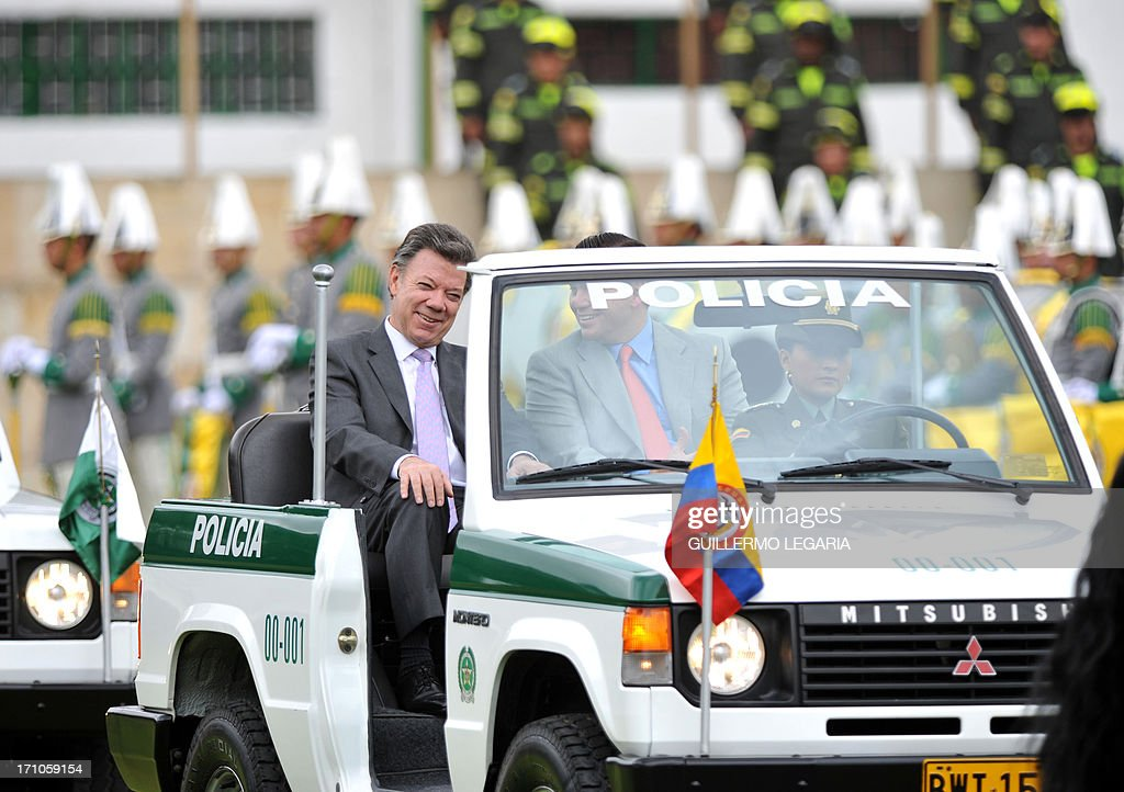 Colombia's President Juan Manuel Santos L), and his Defense Minister Juan Carlos Pinzon review the troops during the promotion ceremony of national police's generals at the General Santander police school in Bogota on June 21, 2013. AFP PHOTO/Guillermo LEGARIA