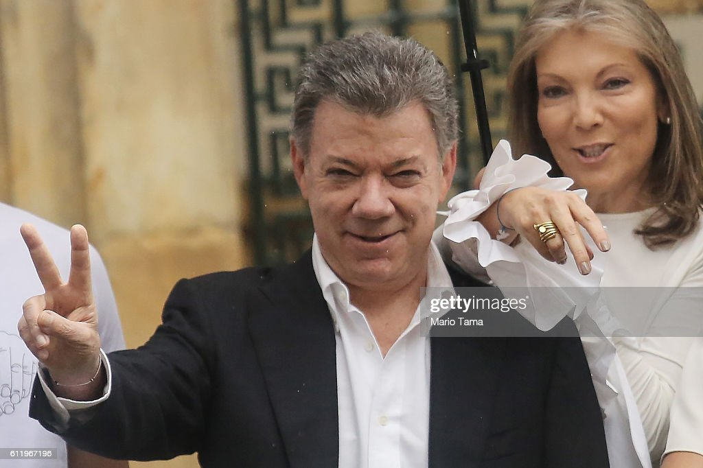 Colombia's President Juan Manuel Santos (C) makes the victory/peace sign with wife Maria Clemencia Rodriguez after voting in the referendum on a peace accord to end the 52-year-old guerrilla war between the FARC and the state on October 2, 2016 in Bogota, Colombia. The guerrilla war is the longest-running armed conflict in the Americas and has left 220,000 dead. The plan calls for a disarmament and re-integration of most of the estimated 7,000 FARC fighters.